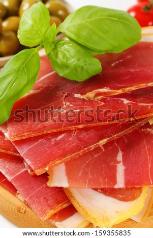slices parma ham with olives and fresh tomatoes - stock photo