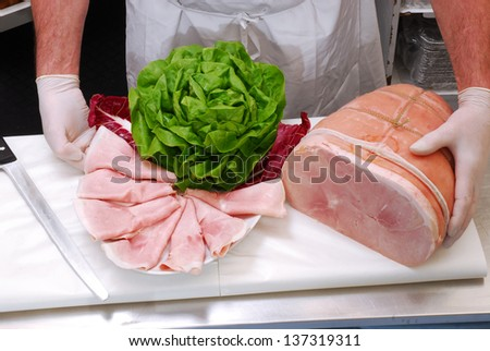 Slicing and preparing prosciutto ham. - stock photo