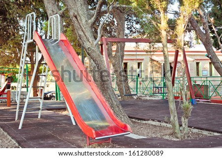Slide and swings in a children's playground - stock photo