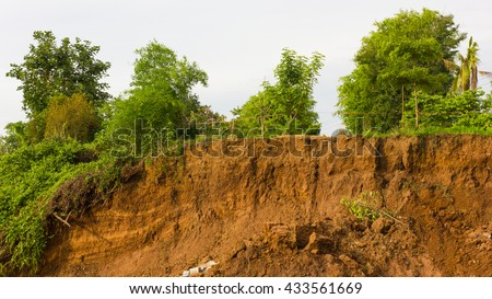 Slide soil erosion caused by groundwater into the river with a tree growing on the ground. - stock photo