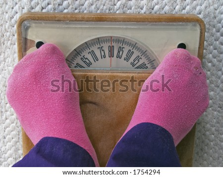 Slight overweight when woman measures her weight - stock photo