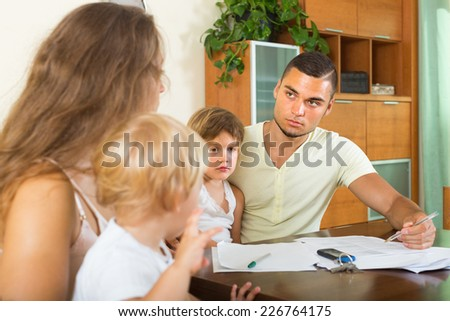 Slight unpleasantness about documents in family with two kids indoor  - stock photo