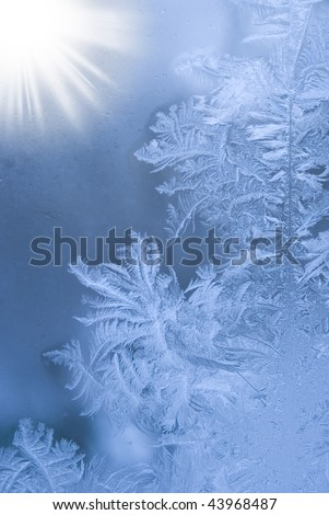 Slightly blurred beautiful frostwork on a window glass (with the sunshine in the left corner) - stock photo