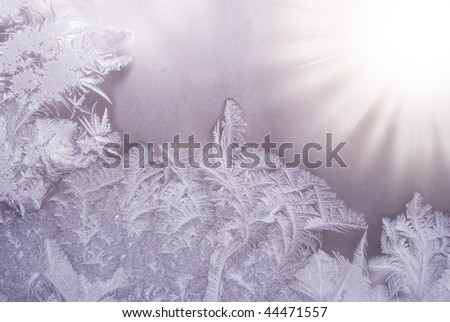 Slightly blurred beautiful frostwork on a window glass (with the sunshine in the right corner) - stock photo