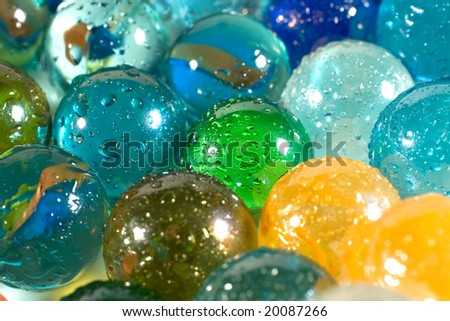 Slightly blurred colorful marbles (with drops of water) as a background