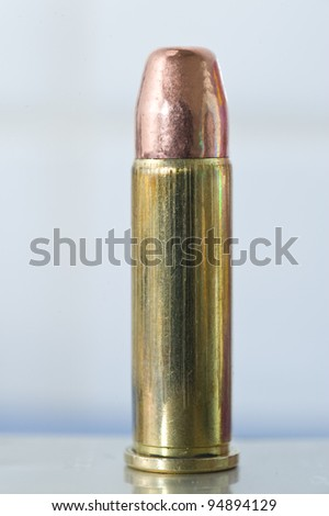 Slightly corroded .38 Special flat point FMJ round on its reflection - stock photo