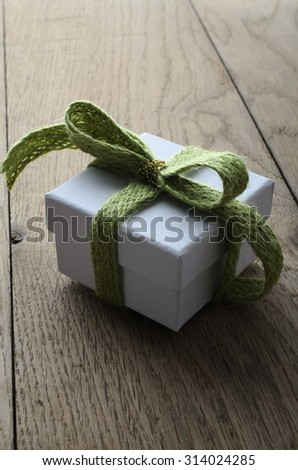 Slightly elevated view of a white, lidded square gift box on an old oak planked table, tied to a bow with a soft green wooly fabric ribbon, and wrapped with a shiny gold thread. - stock photo