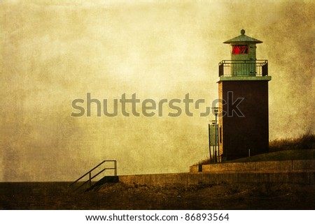 slightly grunge textured picture with a lighthouse at the coast