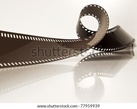 slightly rolled undeveloped film strip on a glossy surface - stock photo