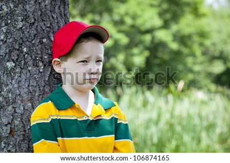 Slightly upset young boy leaning against tree - stock photo
