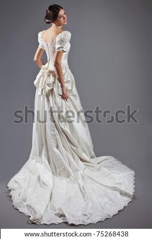 Slim and beautiful woman, wearing luxurious wedding dresses in gray studio - stock photo