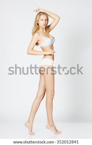 Slim and pure. Full length of attractive young woman in white tank top and panties posing while standing against white background - stock photo