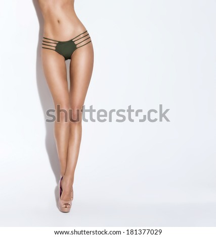 Slim and sexy legs of young and fit girl in fashion swimsuit. - stock photo