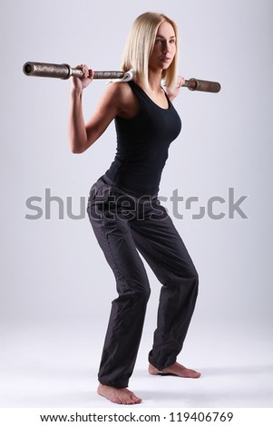 Slim and sporty young blonde doing fitness exercise with fitbar in studio - stock photo