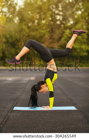 Slim athletic woman doing exercise handstand in the stadium, sporty girl workout, outdoors - stock photo