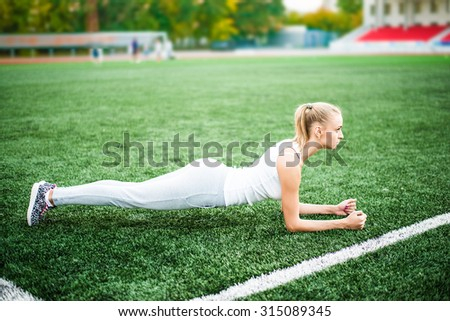 Slim athletic woman doing planking exercise in the stadium on green grass of football field, sporty girl workout, outdoors Blond Female stand on hands Empty space for inscription Full length - stock photo