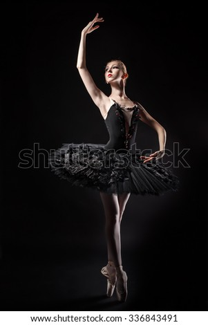 Slim ballerina in a black corset and black tutu. Rehearsal in the theater. Classical Ballet. - stock photo