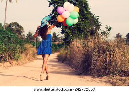 Slim beautiful girl in hat with balloons is going along a dusty road. Vintage style - stock photo