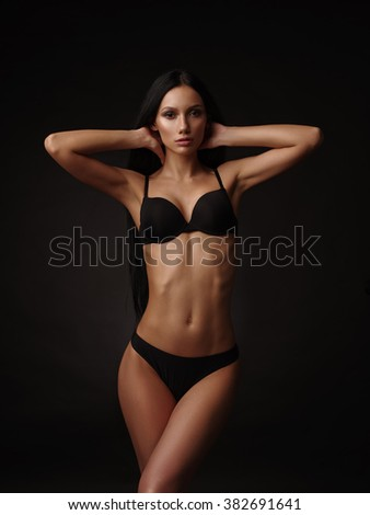 Slim beautiful model with dark straight hair, almond-shaped eyes and tanned skin in the black basic underwear collection is posing in the studio on the black background - stock photo