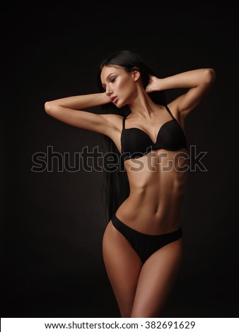 Slim beautiful model with dark straight hair and tanned skin in the black basic underwear collection is posing in the studio on the black background - stock photo