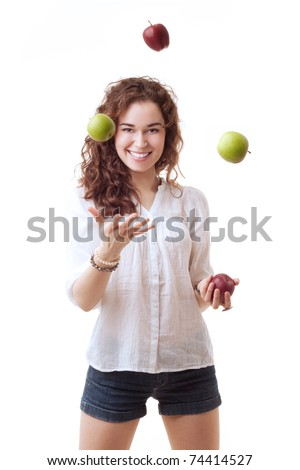 Slim beautiful woman juggling with red and green apples on white background