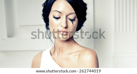 Slim beautiful woman wearing luxurious wedding dress. Bride with beautiful make up and hairstyle is posing against the white wall - stock photo
