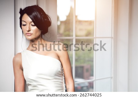 Slim beautiful woman wearing luxurious wedding dress. Bride with beautiful make up and hairstyle is posing against the window - stock photo