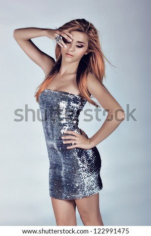slim beautiful woman with long blowing hair on studio background wearing a silver sequin minidress - stock photo