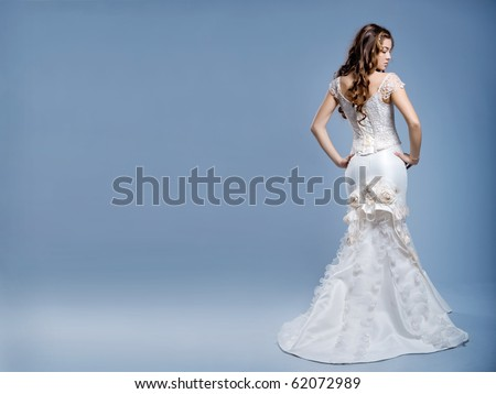 Slim beautiful woman with long hair wearing luxurious wedding dress over gray studio background - stock photo