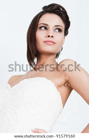 Slim beautiful woman with short hair wearing luxurious wedding dress over white studio background