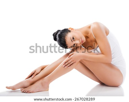 Slim beauty. Beautiful young woman looking at camera and holding hands on her legs while sitting against white background   - stock photo