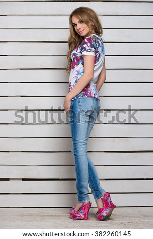 Slim blond woman posing in blue jeans and white flowered t-shirt - stock photo