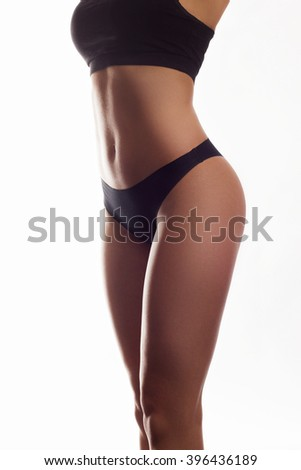 Slim body of the suntanned woman isolated on a white background. Black underwear. Sexual beautiful body. Healthy lifestyle, Diets. - stock photo