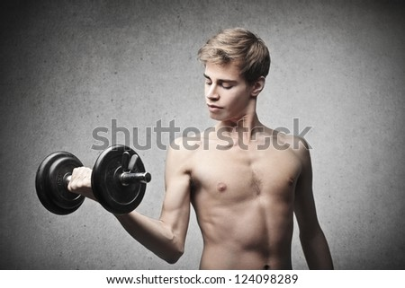 Slim boy exercising with a dumbbell - stock photo