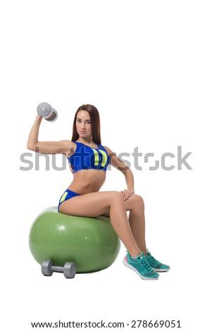 Slim brunette exercising with dumbbells in fitness - stock photo