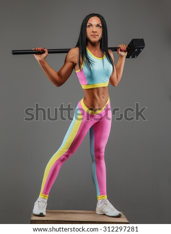 Slim brunette female in colorful sportswear posing over grey background with hummer on her shoulders. - stock photo