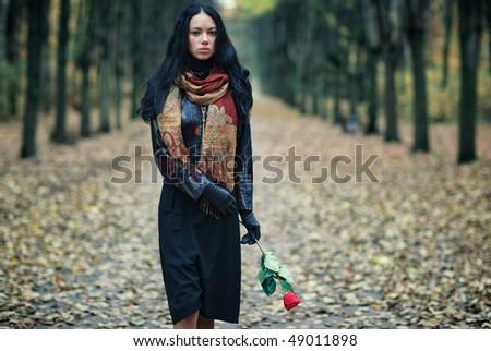 Slim brunette woman in a park. Autumn sadness concept. - stock photo