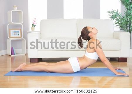 Slim brunette woman lying in yoga pose in her living room on a blue exercise mat