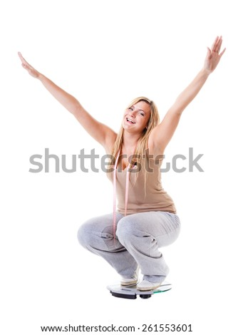 Slim down concept. Woman plus size large content girl on weight scale with measuring tape celebrating weightloss progress after healthy dieting arms up - stock photo