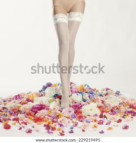 Slim female legs in stockings surrounded by flowers. Conceptual fashion art photo - stock photo