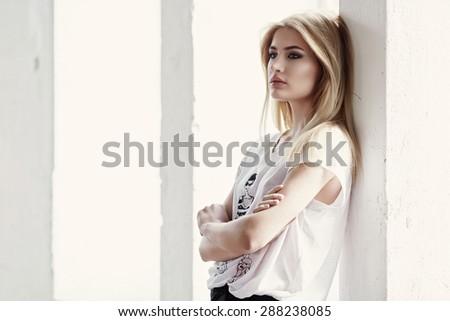 Slim female model posing near wall. - stock photo