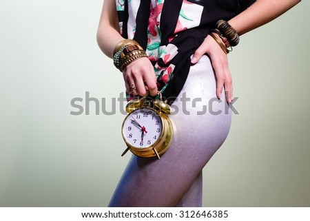 Slim female showing off her legs holding retro alarm clock - stock photo