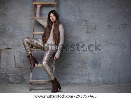 Slim female with long brown hair in shiny clothes posing near wood ladder.