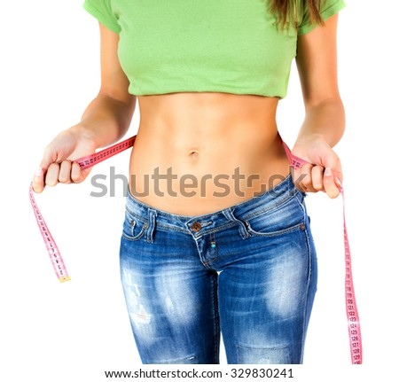 Slim Female with perfect healthy fitness body, measuring her thin waist with a tape measure. Caucasian young woman in jeans. Unrecognizable person.Diet and weight loss concept. - stock photo