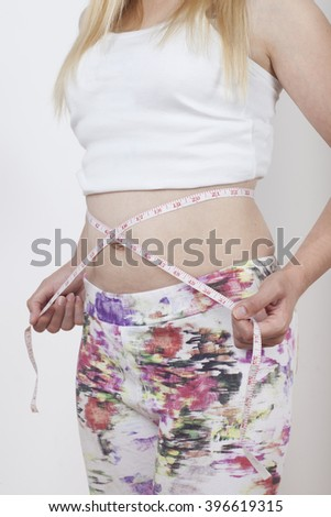 Slim Female with perfect healthy fitness body, measuring her thin waist with a tape measure. Caucasian young woman in jeans, over white background. Diet and weight loss concept. - stock photo