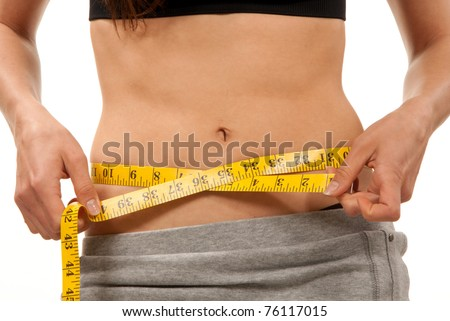 Slim fit body on diet measuring her waist with yellow tape measure and closing  mouth by her hand in ecstatic gesture on a white background - stock photo