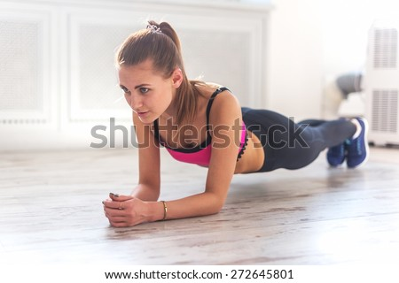 Slim fitnes young girl with ponytail doing planking exercise indoors at home gymnastics. - stock photo