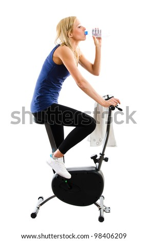 Slim fitness girl drinking mineral water while riding on a training exercise bike