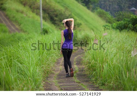 Slim girl in tight sportswear standing outdoors among green grass summer nature, full back view. Tired athletic woman have a rest on the jogging trail.