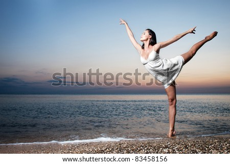 slim girl performing an arabesque at sunset beach - stock photo